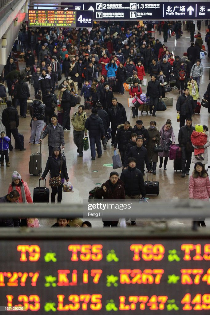 Chinese passengers walk into the Beijing West Railway Station to board trains to go their hometown during the Spring Festival season on January 20, 2012 in Beijing, China. Chinese people are preparing for the lunar new year of Dragon, which will fall on January 23, 2012. New year celebrations are also refered to as The Spring Festival.