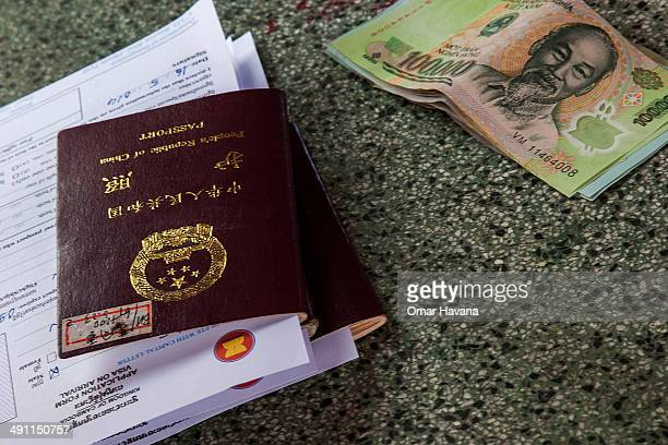 Chinese passport and some Vietnamese Dongs are left on one of the tables of the customs office for a Cambodian visa application on May 16 2014 at the...