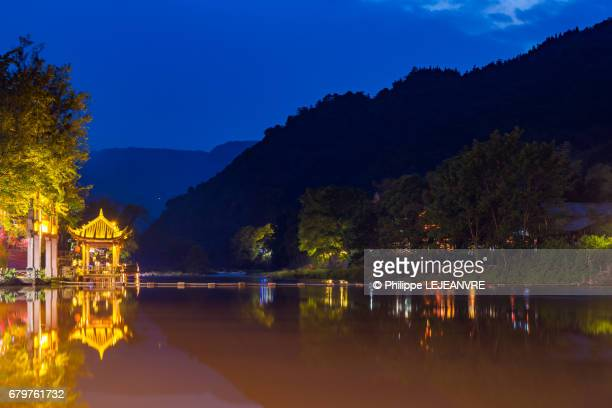 Chinese pavilion reflecting in the river at night in the mountains