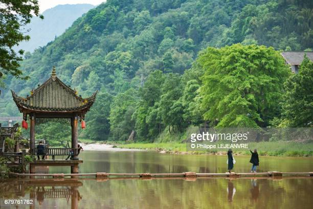 Chinese pavilion reflecting in the river with two people crossing a bridge
