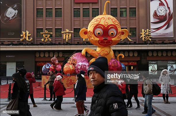 Chinese pedestrians walk passed a display for the upcoming Year of the Monkey for the Chinese New Year at a market on January 19 2016 in Beijing...