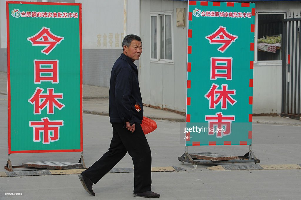 Chinese pedestrians walk past a notice saying 'Closed today' in Huishang Wholesale Poultry Market after positive samples of H7N9 were found at the market in Hefei, central China's Anhui province on April 11, 2013. The number of cases of the H7N9 strain of avian influenza rose to 33 on April 10, with nine deaths since China announced over a week ago that it had been found in humans for the first time. CHINA OUT AFP PHOTO