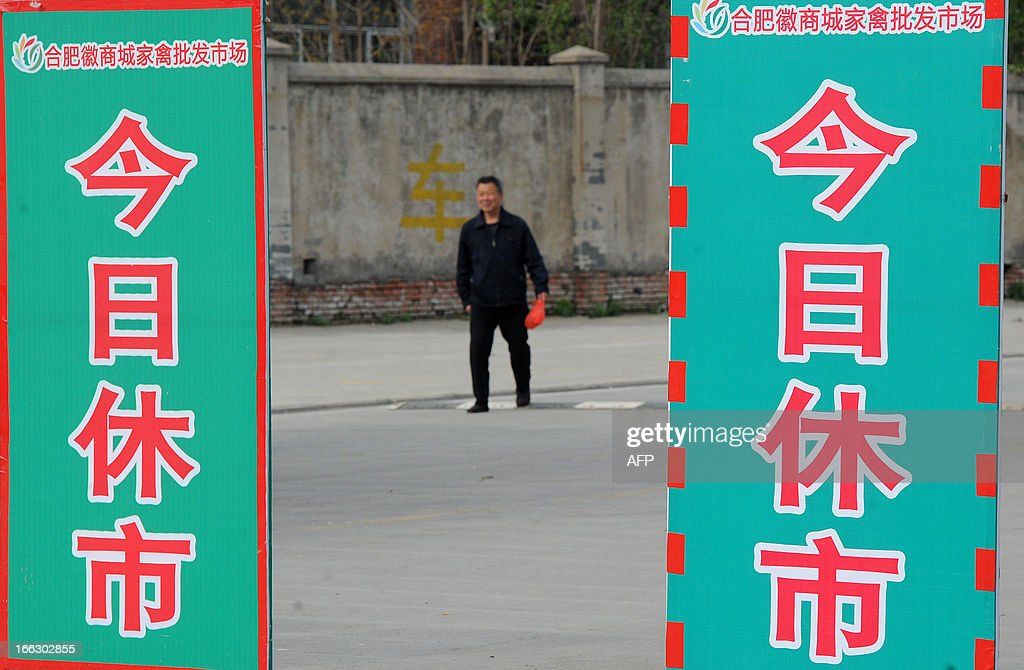 Chinese pedestrians walk past a notice saying 'Closed today' in Huishang Wholesale Poultry Market after positive samples of H7N9 were found at the market in Hefei, central China's Anhui province on April 11, 2013. The number of cases of the H7N9 strain of avian influenza rose to 33 on April 10, with nine deaths since China announced over a week ago that it had been found in humans for the first time. CHINA