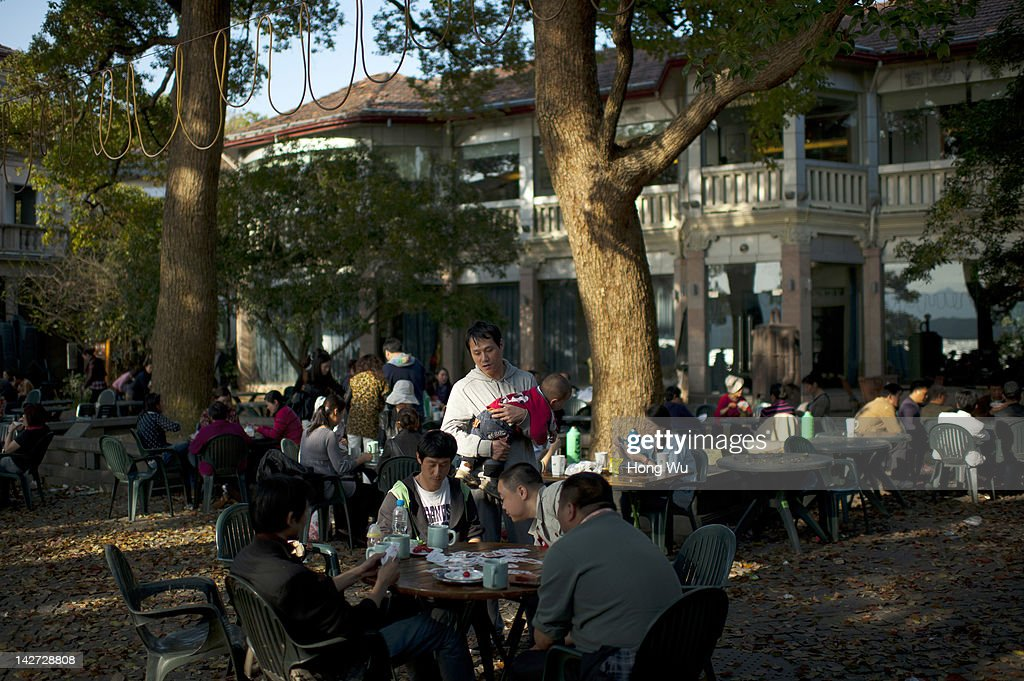 Chinese people gather to play cards and enjoy Longjing tea at an outdoor teahouse beside West Lake on April 01, 2012 in Hangzhou, China. Longjing is a green-tea, often called Dragon Well tea. The tea is typically picked by hand, and is of a high quality, earning the title of China Famous Tea. The Longjing tea begins to pluck before Chinese traditional Qingming Festival, the 15th day from the Spring Equinox or usually occurring around April 5. Many Chinese migrant workers from Jiangsu, Anhui, Jiangxi and other neighboring provices have been employed with 80 RMB yuan(US$12.68) to 120 RMB yuan(US$ 19.03) per day to pluck fresh Longjing tea leaves for villagers in many Longjing tea production villages in the outskirts of Hangzhou. The price of Longjing tea rose in recent years which aims to become to luxury goods. A high-end Longjing tea in Hangzhou sold for 50,000 RMB yuan(US$ 7930) half a kilo in 2012, the price rose 70 times in the last 12 years.