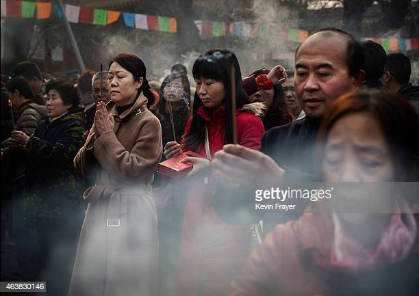 Chinese people hold incense as they pray with others at the Yonghegong Lama Temple during celebrations for the Lunar New Year February 19 2015 in...