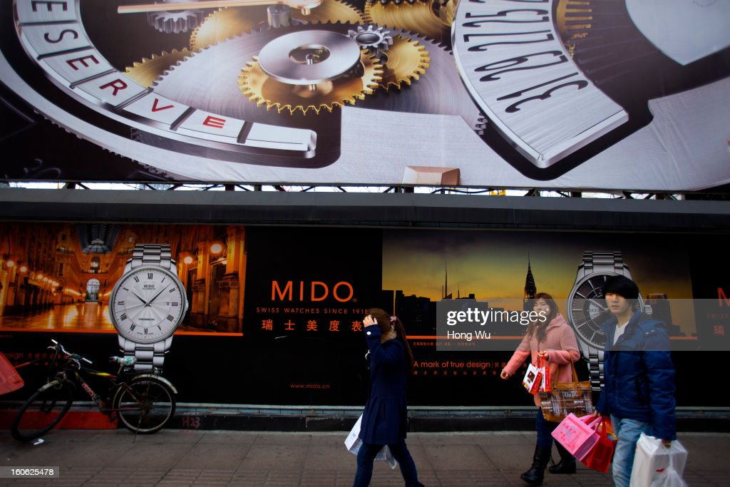 Chinese people pass by a clock billboard on February 3, 2013 in Shanghai, China.