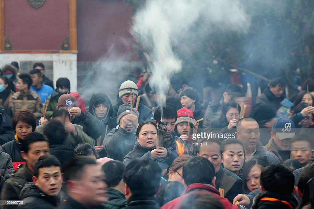Chinese people pray for good fortune as they hold burning incense on the first day of the Chinese Lunar New Year at Yonghegong Lama Temple on January 31, 2014 in Beijing, China. The Chinese Lunar New Year of Horse also known as the Spring Festival, which is based on the Lunisolar Chinese calendar, is celebrated from the first day of the first month of the lunar year and ends with Lantern Festival on the Fifteenth day.
