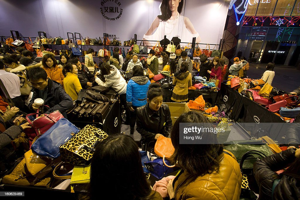 Chinese people purchase handbags at a stall in Nanjing Road Walking Street on February 3, 2013 in Shanghai, China.