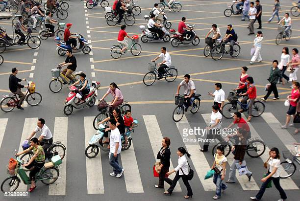 Chinese people ride bicycles and walk past a crossroad on May 26 2005 in Chengdu of Province China China's economy is growing steadily and its...