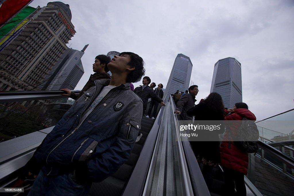 Chinese people view high buildings on an escalator on February 3, 2013 in Shanghai, China.