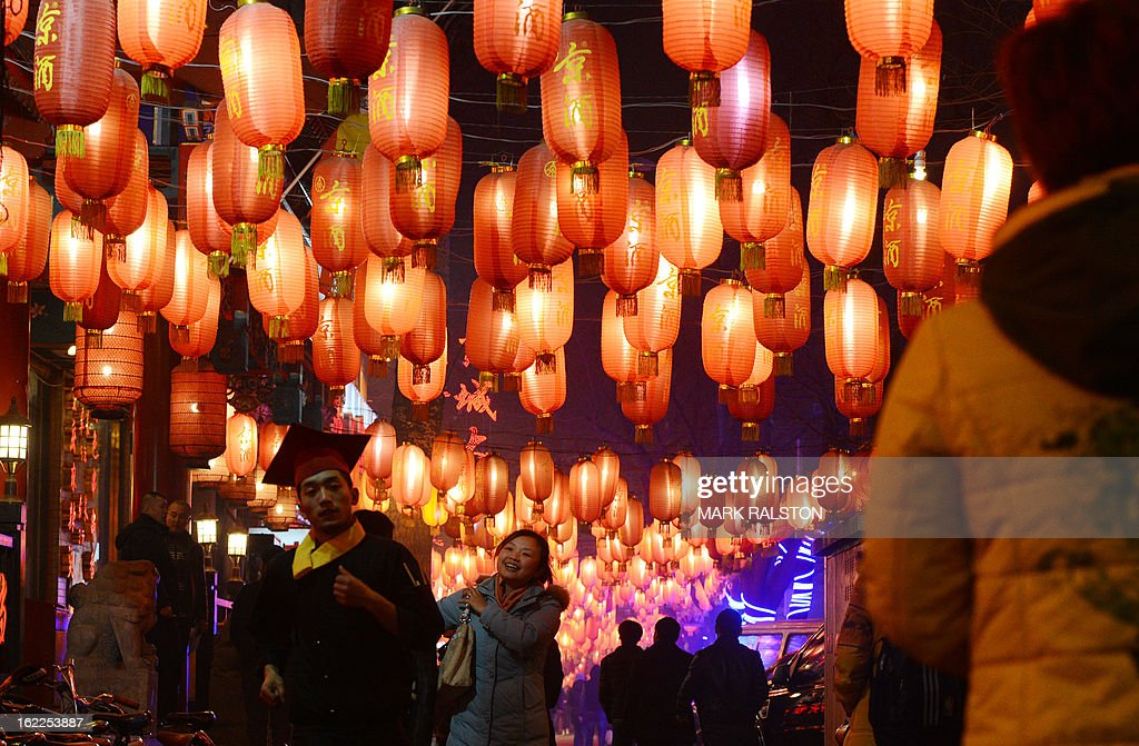 Chinese people walk beneath lanterns as the city prepares for the traditional Lantern Festival which falls on the 15th day of the Lunar New Year and officially ends the celebrations, in Beijing on February 21, 2013. The festival which dates back more than 2000 years to the Han Dynasty sees China's cities becoming a sea of lanterns and fireworks. AFP PHOTO/Mark RALSTON