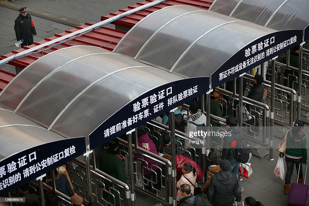 Chinese people walk with their luggage at the entrance of the check-in kiosks for real-name tickets as a policeman looks at Beijing West Railway Station on January 8, 2012 in Beijing, China. China's annual Spring Festival travel rush begins on Sunday, and authorities estimate 3.158 billion passenger journeys will be made for the Chinese lunar new year during the 40-day travel period.