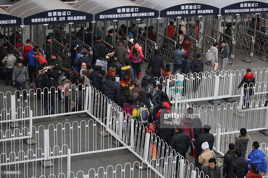 Chinese people walk with their luggage at the entrance of the check-in kiosks for real-name tickets at Beijing West Railway Station on January 8, 2012 in Beijing, China. China's annual Spring Festival travel rush begins on Sunday, and authorities estimate 3.158 billion passenger journeys will be made for the Chinese lunar new year during the 40-day travel period.