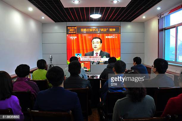 Chinese people watch live television coverage at a conference room in Yantai east China's Shandong province as Chinese Premier Li Keqiang delivers...