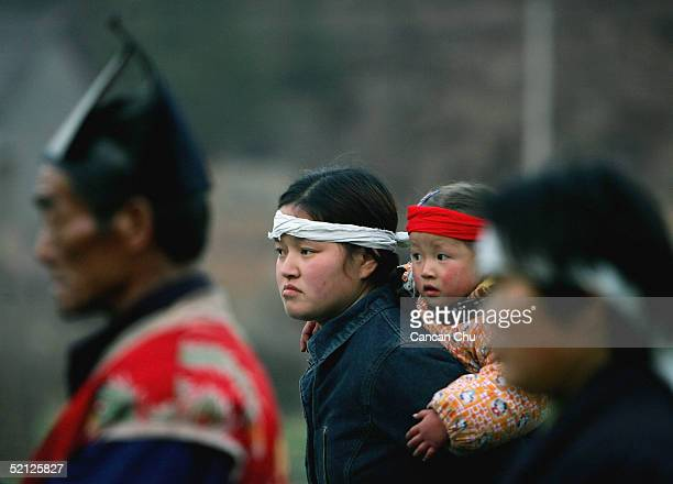 Chinese people wearing a white or red band around their heads attend the funeral of a relation on February 2 2005 in Jinzhai County Anhui Province...