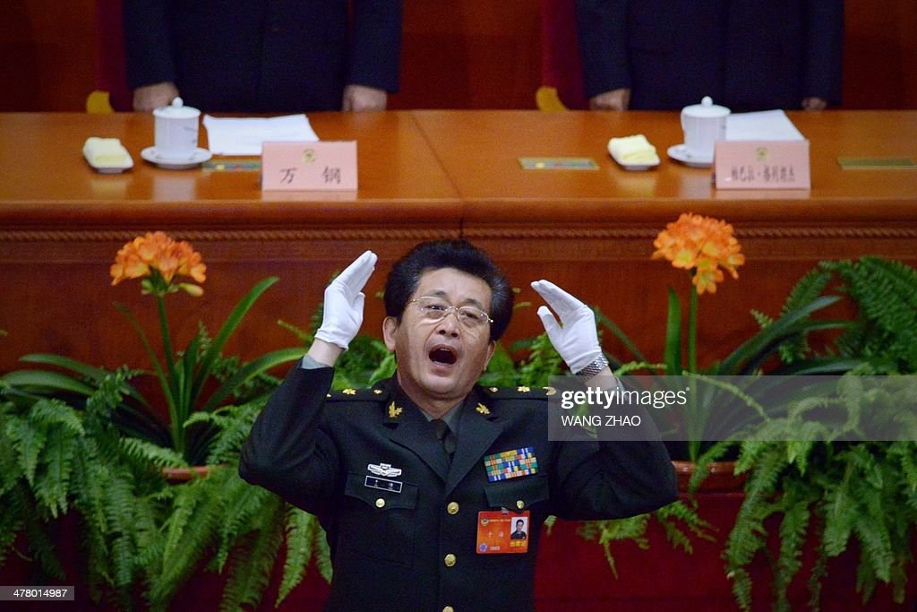 A Chinese People's Liberation Army (PLA) officer conducts delegates singing the national anthem at the closing session of the Chinese People's Political Consultative Conference (CPPCC) at the Great Hall of the People in Beijing on March 12, 2014. China has banned delegates to its annual rubber-stamp parliament from holding banquets, an official said as the government tries to improve its image following regular corruption scandals.