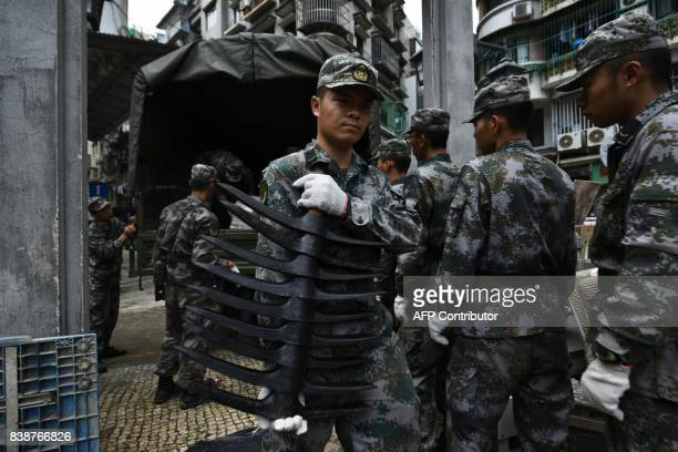 Chinese People's Liberation Army soldiers based at a barracks in Macau unload hardware tools as they help clear debris in Macau on August 25 two days...