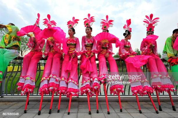 Chinese performers wait in front of the National Stadium also know as the 'Bird's Nest' prior a full dress rehearsal for the Beijing 2008 Olympics on...