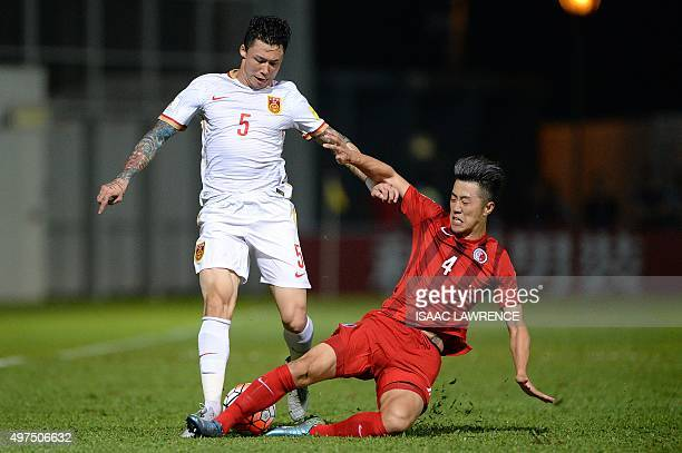 Chinese player Zhang Linpeng is tackled by Hong Kong player Bai He during a World Cup qualifier at Mong Kok stadium in Hong Kong on November 17 2015...