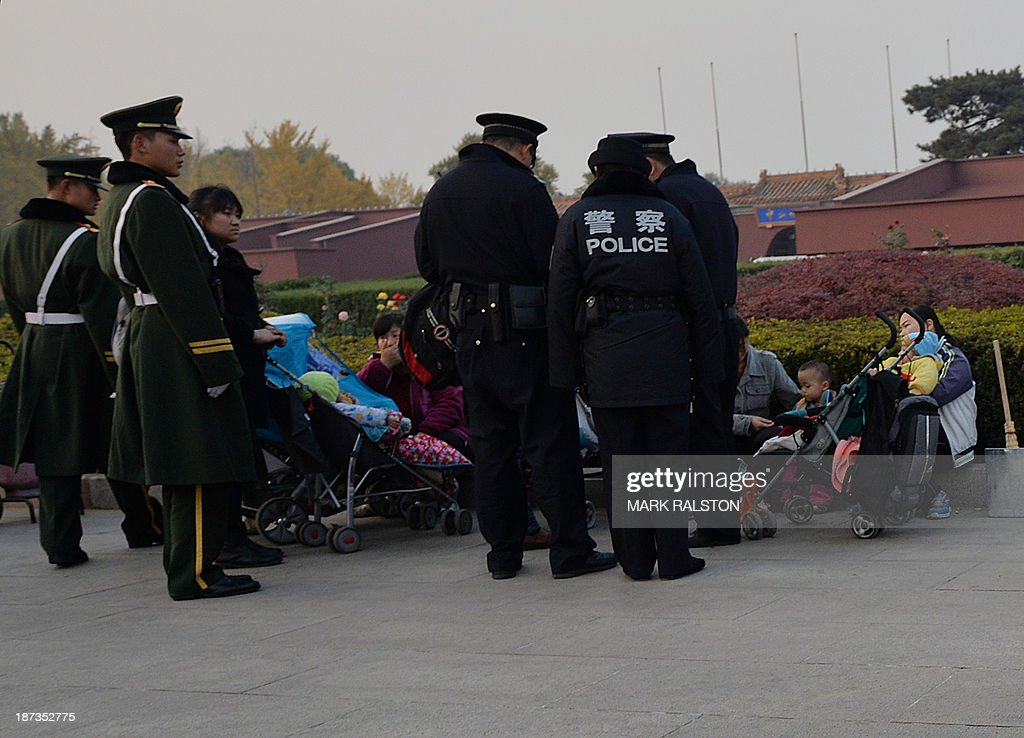 Chinese police and para-military police question a group of young mothers at Tiananmen Square as security is incresed on the eve of an important Communist Party Congress in Beijing on November 8, 2013. China's new leadership holds a key meeting this weekend that state media are trumpeting as a likely 'watershed' for economic reform, but analysts caution details of its decisions are likely to be vague and implementation gradual. The four-day session of the full 376-strong Communist Party Central Committee begins November 9 at a closely guarded private hotel in Beijing. AFP PHOTO/Mark RALSTON