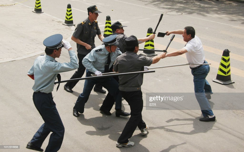 Chinese police and security personnel undergo a drill to protect students from an 'attacker' outside a school in Liaoning, northeast China's Shenyang province on May 27, 2010. Communities across the country have taken a number of measures, including beefing up school security forces, and shutting down bars and other entertainment venues near schools, as five separate attacks in recent weeks on young children by mentally disturbed assailants have shocked China. CHINA