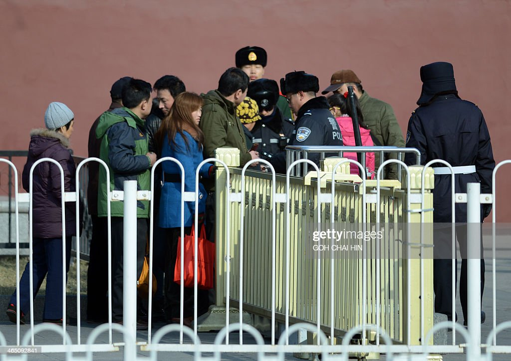 Chinese police check IDs of visitors arriving at the Tiananmen Gate in Beijing on January 26, 2014, after police said three Uighurs drove a vehicle into crowds of tourists opposite Beijing's Tiananmen Square -- the symbolic heart of the Chinese state -- killing two people and injuring 40, in late October 2013. Six people died in explosions and another six were shot dead by police in China's Xinjiang, authorities said on January 25, in the latest wave of violence to hit the restive region.