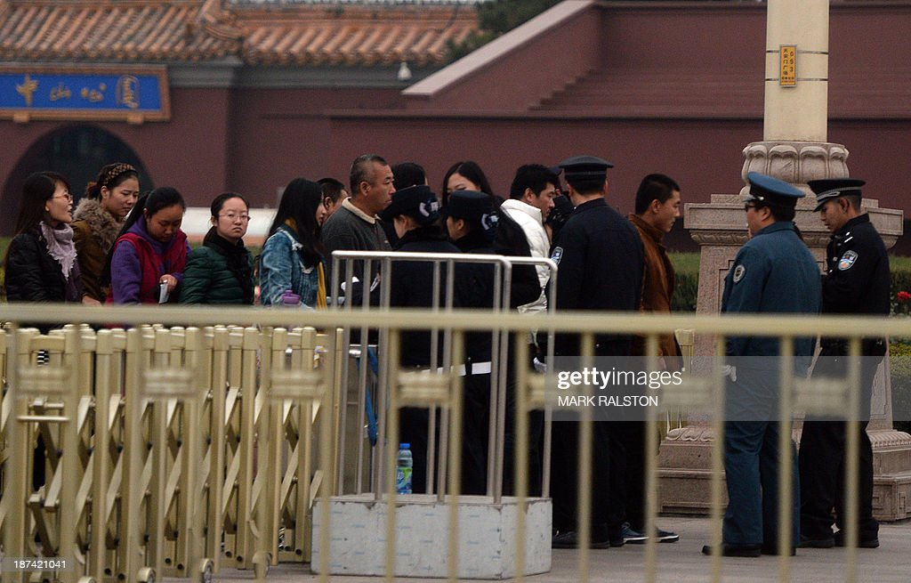 Chinese police check tourists entering Tiananmen Square as security is increased during the Communist Party Central Committee's Third Plenum in Beijing on November 9, 2013. China's ruling Party started the key meeting which is expected to focus on economic reforms a year after a closely watched leadership transition. The four-day session of the full 376-member Communist Party Central Committee takes place at a closely guarded private hotel and traditionally sets the economic tone for a new government. AFP PHOTO/Mark RALSTON