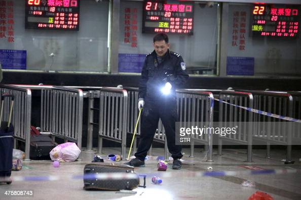 A Chinese police investigator inspects the scene of an attack at the railway station in Kunming southwest China's Yunnan province on March 2 2014 A...