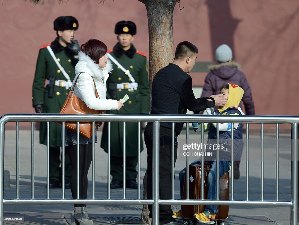 Chinese police keep a watchful eye on a family as they arrive at the Tiananmen Gate in Beijing on January 26, 2014, after police said three Uighurs drove a vehicle into crowds of tourists opposite Beijing's Tiananmen Square -- the symbolic heart of the Chinese state -- killing two people and injuring 40, in late October 2013. Six people died in explosions and another six were shot dead by police in China's Xinjiang, authorities said on January 25, in the latest wave of violence to hit the restive region.