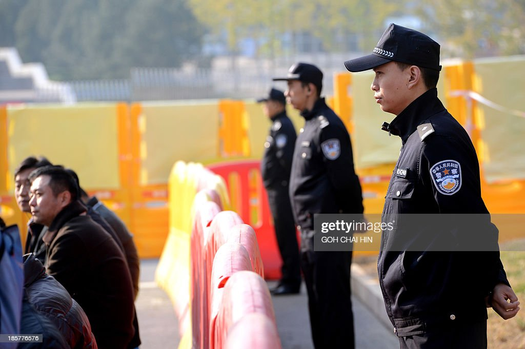 Chinese police keep watch on members of the media outside the gate of the Shandong high court building in Jinan, east China Shandong province on October 25, 2013. The court will deliver the ruling on the appeal of once-powerful politician Bo Xilai -- formerly one of the country's top 25 leaders, who ran the southwestern megacity of Chongqing -- was sentenced to life in prison in September by the Intermediate People's Court in Jinan. AFP PHOTO/GOH CHAI HIN