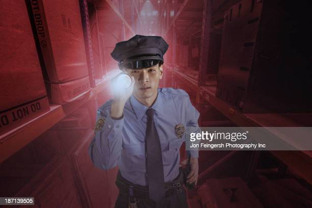 Chinese police officer shining flashlight in warehouse