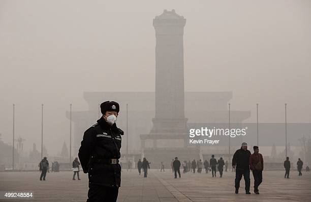 Chinese police officer wears a protective mask as he stands in a very hazy Tiananmen Square on a day of heavy pollution on November 30 2015 in...