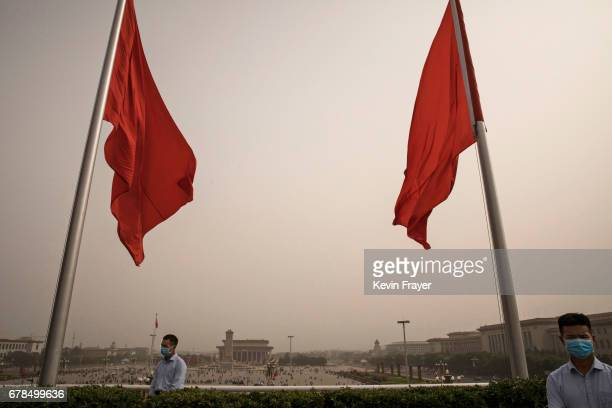Chinese police officers wear masks to protect from particles blown during a sandstorm as they stand guard overlooking Tiananmen Square on May 4 2017...