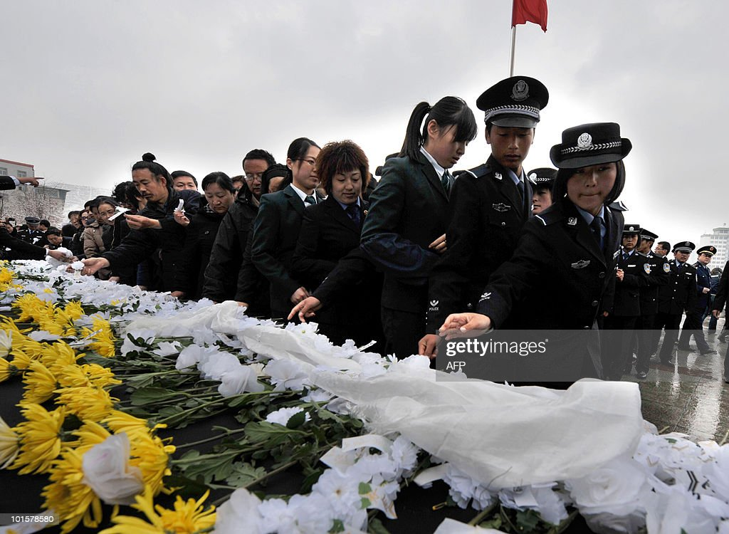 Chinese police place flowers as they take part in a mourning ceremony in Xining, northwest China's Qinghai province, as China observed a day of national mourning on April 21, 2010 for victims of the recent quake. Top leaders and thousands of other people paid a silent tribute to the victims of the 6.9 magnitude earthquake which struck a remote area of northwestern China on April 14, 2010, leaving at least 2,064 people dead. CHINA