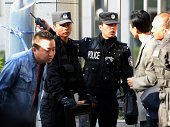 Chinese police screen people who want to enter the Urumqi Intermediate People's court as the trial of Ilham Tohti a former economics professor at a...