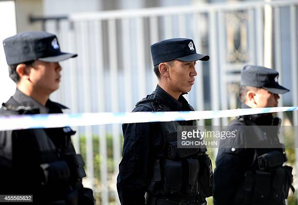 Chinese police seal off the road leading to the Urumqi Intermediate People's court as the trial of Ilham Tohti a former economics professor at a...