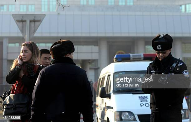 Chinese police stop a foreign journalist outside the No 1 Intermediate court on January 22 as strict security was imposed ahead of the trial of Xu...