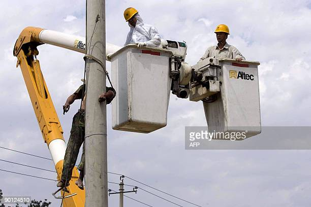 Chinese police try to bring down a worker who died after he was aparently electrocuted while working on an electricity pole in Beijing on August 27...