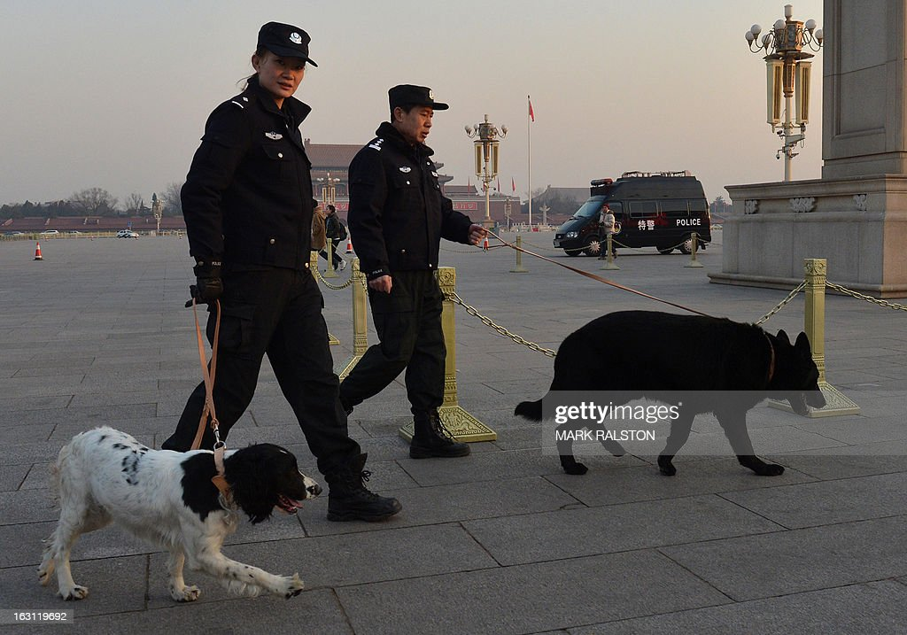 Chinese police use sniffer dogs before the opening session of the National People's Congress (NPC) at the Great Hall of the People (background) in Beijing on March 5, 2013. Thousands of delegates from across China were meeting this week to seal a power transfer to new leaders whose first months running the Communist Party have pumped up expectations with a deluge of propaganda. AFP PHOTO/Mark RALSTON