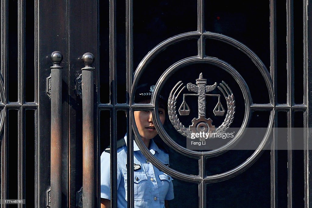 A Chinese police woman looks out the gate of the Jinan Intermediate People's Court on August 23, 2013 in Jinan, China. Ousted Chinese politician Bo Xilai is standing trial on charges of bribery, corruption and abuse of power for a second straight day. Bo Xilai made global headlines last year when his wife Gu Kailai was charged and convicted of murdering British businessman Neil Heywood.