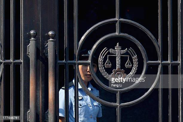 Chinese police woman looks out the gate of the Jinan Intermediate People's Court on August 23 2013 in Jinan China Ousted Chinese politician Bo Xilai...