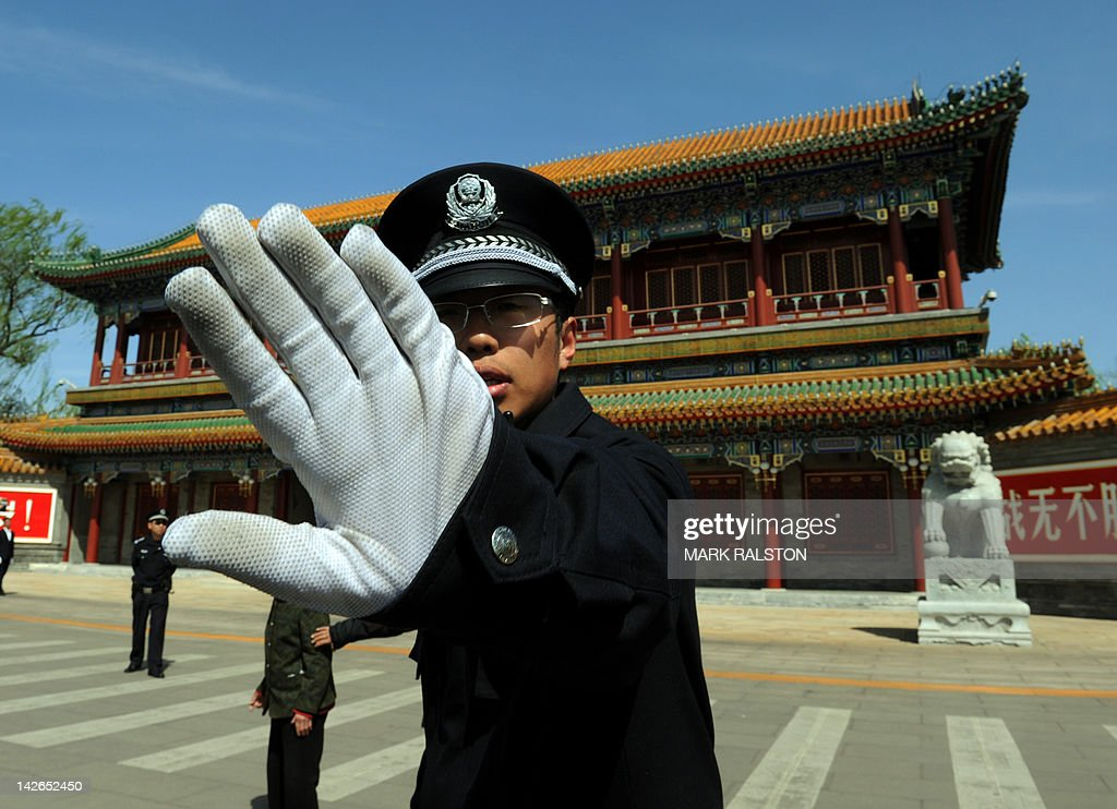 A Chinese policeman blocks photos being taken outside Zhongnanhai which serves as the central headquarters for the Communist Party of China after the sacking of politician Bo Xilai from the countries powerful Politburo, in Beijing on April 11, 2012. Once a rising political star known for busting gangs and reviving Maoist ideals, China's Bo Xilai has suffered a dramatic fall from grace that now sees him linked to a suspected murder. The 62-year-old was once a leading contender to enter the top rungs of power, but in a stunning reversal of fortune he was sacked as head of Chongqing city and late Tuesday suspended from the Communist Party's powerful Politburo. AFP PHOTO/Mark RALSTON