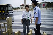 A Chinese policeman checks pedestrians at an entrance to Tiananmen Square in Beijing on September 1 prior to a military parade to be held on...