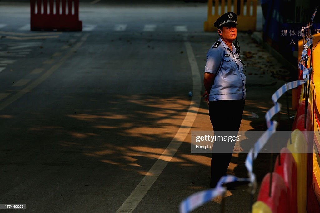 A Chinese policeman guard outside the gate of the Jinan Intermediate People's Court on August 23, 2013 in Jinan, China. Ousted Chinese politician Bo Xilai is standing trial on charges of bribery, corruption and abuse of power for a second straight day. Bo Xilai made global headlines last year when his wife Gu Kailai was charged and convicted of murdering British businessman Neil Heywood.