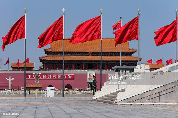 Chinese policeman guards in front of a giant portrait of the late chairman Mao Zedong at Tiananmen Square before the closing ceremony of the Chinese...