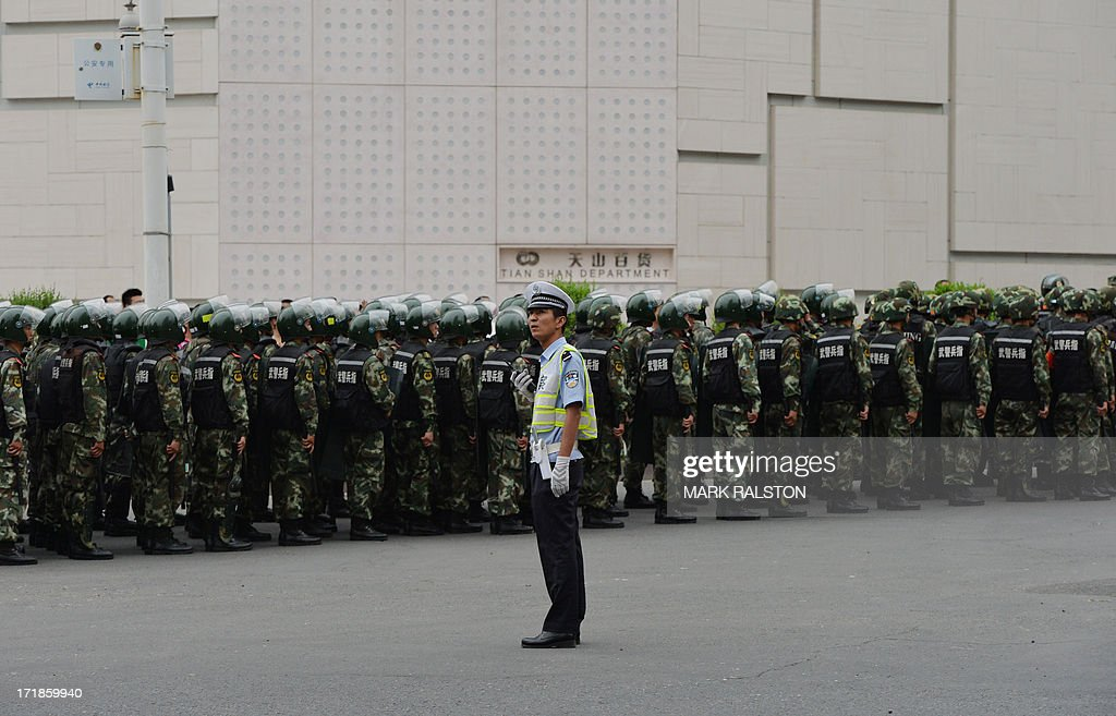 A Chinese policeman keeps watch as paramilitary police prepare to ride in armoured vehicles during a 'show of force' ceremony in Urumqi after a series of terrorist attacks recently hit Xinjiang Province, on June 29, 2013. Armoured vehicles, personnel carriers and other support vehicles blocked access to streets in Xinjiang's capital Urumqi, where paramilitary units carried out an exercise. The exercises come ahead of the fourth anniversary on July 5 of riots, between members of China's mostly Muslim Uighur ethnic minority and the Han majority group, which left around 200 dead. AFP PHOTO/Mark RALSTON