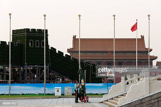 Chinese policeman stands guard in front of a giant portrait of the late chairman Mao Zedong at Tiananmen Square on August 14 2015 in Beijing China...