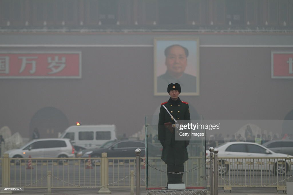 A Chinese policeman stands guard on the Tiananmen Square which is shrouded with heavy smog on January 16, 2014 in Beijing, China. Beijing Municipal Government issued a yellow smog alert this morning.