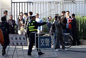 A Chinese policeman tries to control the crowd waiting to be allowed to enter the Urumqi Intermediate People's court as the trial of Ilham Tohti a...