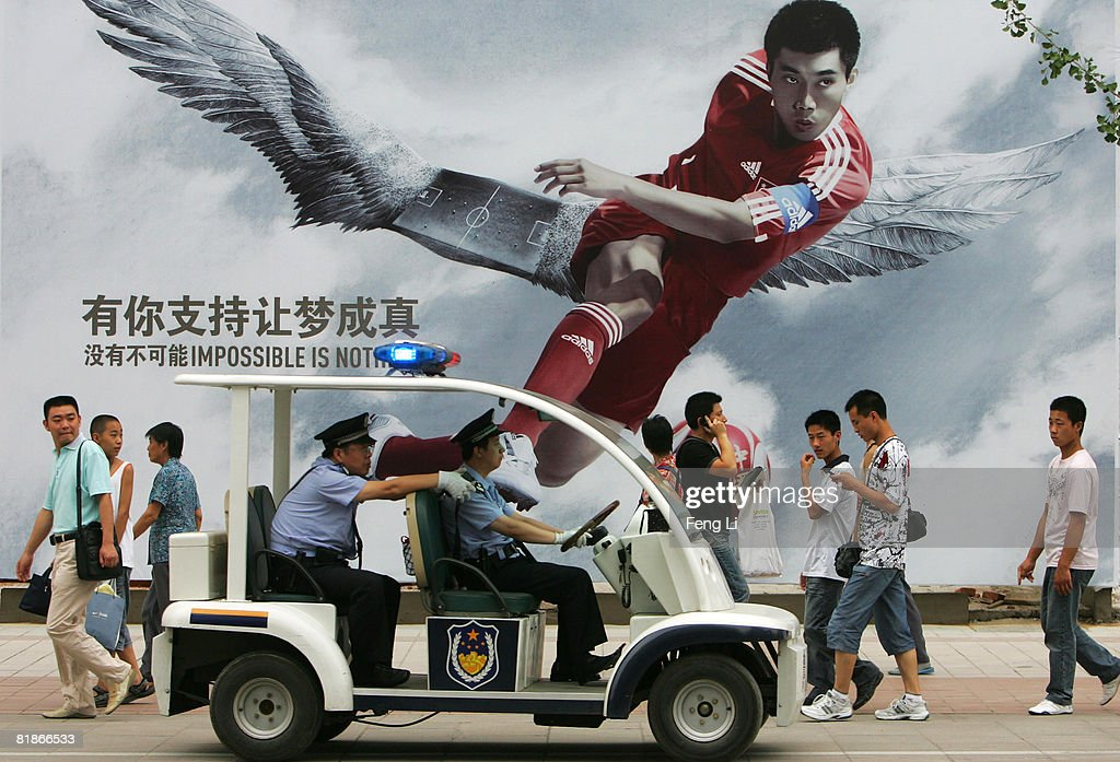 Chinese policemen drive a police car in front of a billboard depicting Chinese football player Zheng Zhi July 2, 2008 in Beijing, China. Beijing will host the 2008 Olympics from August 8 to 24, 2008.